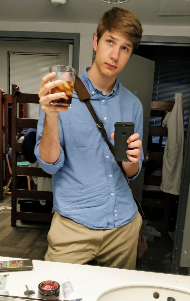 Matthew Krupczak looking in a mirror holding iced coffee